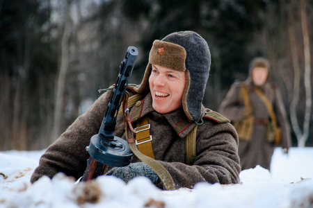 NELIDOVO, MOSCOW REGION, RUSSIA - JANUARY 22, 2017: Reconstruction of the winter defensive battles of the Red Army of the 1st Ukrainian Front in WWII called Battlefield. Hot snow (1944 year). Smiling Red army infantry soldier with his PPSh submachine gu
