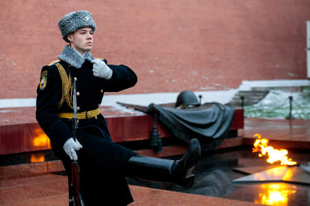 MOSCOW, RUSSIA - DECEMBER 04, 2019: Hourly change of the Presidential guard of Russia at the Tomb of Unknown soldier and Eternal flame in Alexander garden near Kremlin wall in winter uniform Editorial