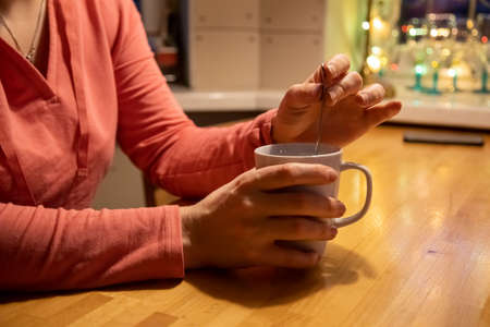 close-up female hands hold a white cup with a warm drink and mix with a teaspoon on a wooden table. The concept of comfort and warmth. soft focus, blur background Stock fotó