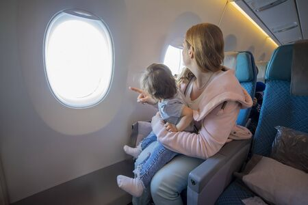 young beautiful mother sits in an airplane chair holds on her lap a little cute baby and shows him to look into the porthole Foto de archivo