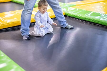 happy toddler girl in a dress jumping on a trampoline next to dad at a childrens playground in a childrens play center. blur background