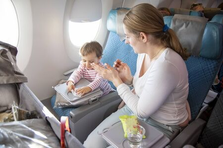 a little cute toddler girl sitting in an airplane in a chair by the porthole herself wipes a folding table with a wet antibacterial napkin before eating. mom applauds and praises the child