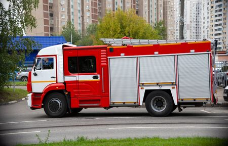 A fire truck is driving an emergency call on a road in the city. side view Stock Photo