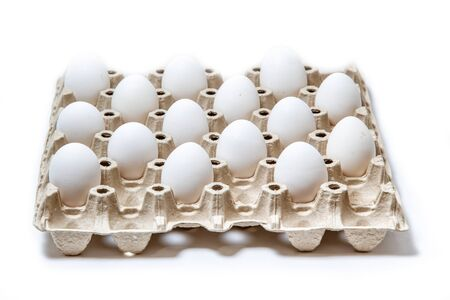 isolated carton box with distanced white eggs. concept of quarantine rules