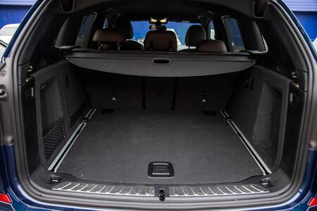 Family car empty car boot with luggage space available. Empty car boot car trunk with boot lid open on a family car, Rear view of a car with an open trunk, close up, soft focus, blurred background