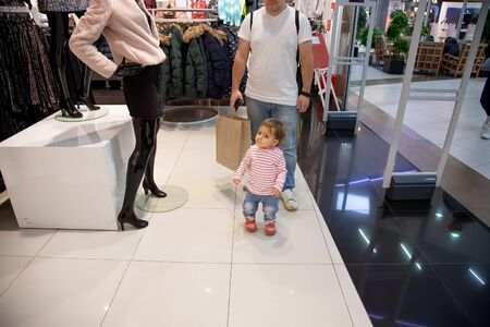 black friday sale concept , shopping with children. little cute baby girl standing in clothing store in front of mannequin. behind is dad with a paper bag for shopping. soft focus, blur background