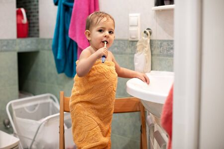 little cute baby, 1,3 year old, is standing on a chair in the bathroom wrapped in an orange towel with a toothbrush and brushes his teeth and looks at the camera. close-up, soft focus Archivio Fotografico