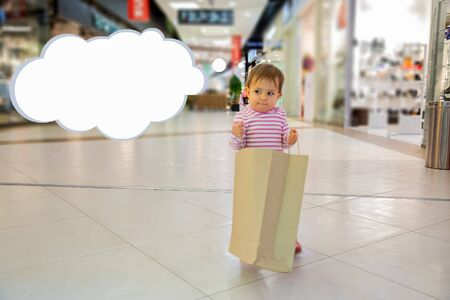 Black friday concept, shopping with children. little cute baby girl holds craft paper bag for shopping and smiles slyly, Thought Bubble for copy space. close-up, soft focus, in the background shops Zdjęcie Seryjne
