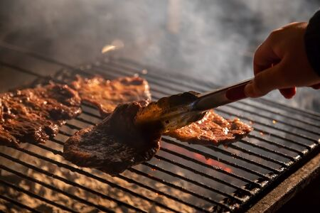 in the evening a barbecue grill on which tasty juicy steaks are grilled over an open fire, a hand holds tongs and turns the meat over. close-up, soft focus. smoke is highlighted Foto de archivo