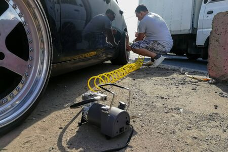 accident on the road: flat tire pressure. a man inflates a passenger car wheel with a compressor with a long yellow hose. close-up Banco de Imagens