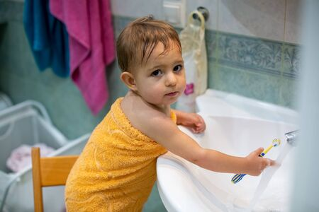 little cute baby, 1 year old, stands on a chair in the bathroom wrapped in an orange towel washes a toothbrush in the sink under the tap with water. looking at the camera. close-up, soft focus