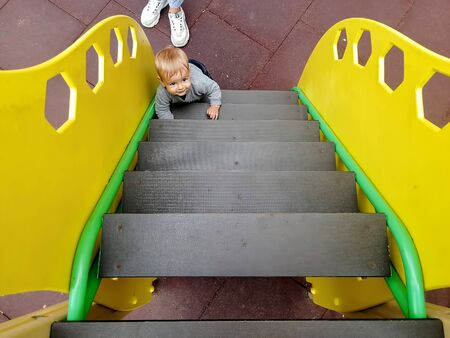 A little cute Caucasian baby climbs the yellow stairs on a childrens playground. on the floor on a rubberized safe cover is the mother of the baby. top view, close-up Zdjęcie Seryjne