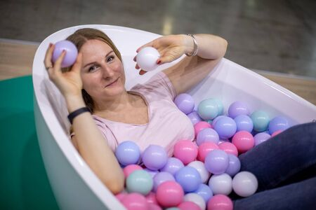 A young Caucasian girl is lying in a bath with multi-colored plastic balls, smiling and looking at the camera holding balls in her hands. close-up, soft focus 版權商用圖片