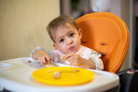 cute baby in an orange child seat tilted his head and looks at the camera, holding a pie in his hands. crumbs and an orange plate on the table. close-up, front view, soft focus, blur background
