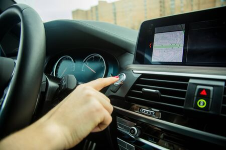 female hand with finger presses the start stop engine button on a car dashboard. close-up, soft focus, in the background car interior details in blur, side view