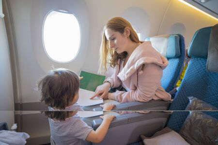 a young beautiful mother sits in an airplane chair shows with finger a page in a book to her little cute toddler, who is standing in front of her. close-up, soft focus,copy space, blank page