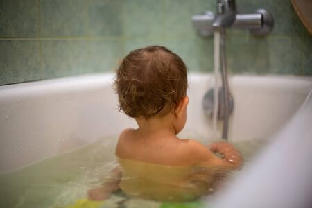 A cute Caucasian baby takes a bath sits in water with his back to the camera. close-up, soft focus, blur background.
