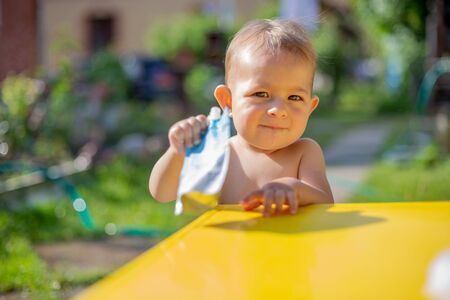 baby holds fruit puree in pouch and looking into the camera and gives it to camera in front of the yellow table. on the background is a green garden on a sunny day in blur. close up 版權商用圖片