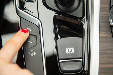 the finger of a female hand hush to the parking assistant button, the equipment of a modern car. close-up, soft focus, blur background Фото со стока