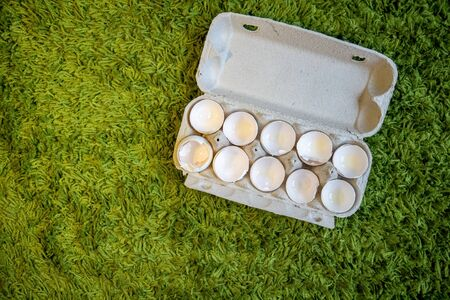 10 broken empty egg shells lie in a box on artificial grass. top view, close-up, place for copyspace. Фото со стока