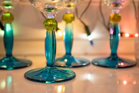 close-up of blue legs of glass goblets on a white table. garland flickers in the background Foto de archivo