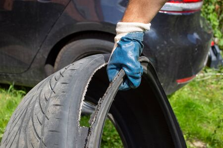 recycle of tires, ecology. the hand of the master in a blue glove holds the torn tire. on the background black car in blur Stock Photo