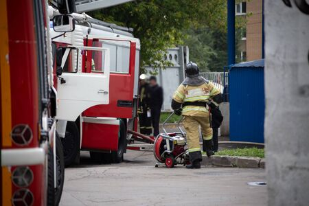 firefighter stands with his back near the fire engines, resting after the fire. background in blur