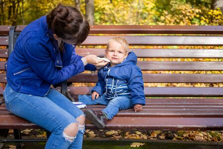 little cute baby in blue clothes sits on a bench in the park, looks at the camera seriously, while Mom wipes his dirty face with a napkin. close-up, on background are autumn trees in blur.