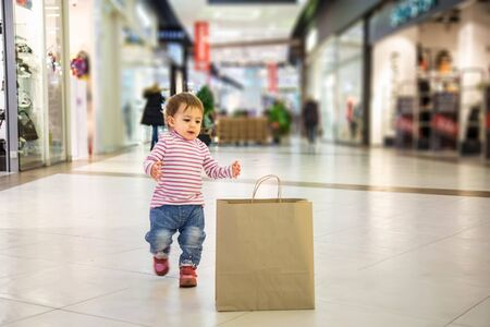 smart nature friendly shopping concept. Close up of eco friendly paper bag. little cute baby girl run to a paper bag for shopping in the mall . soft focus, blur background