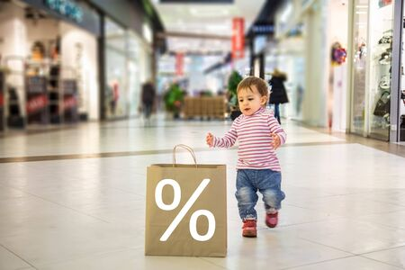 smart nature friendly black friday sale shopping concept. Close up of little cute baby girl run to eco friendly paper bag for shopping in the mall with percent sign. soft focus, blur background Imagens