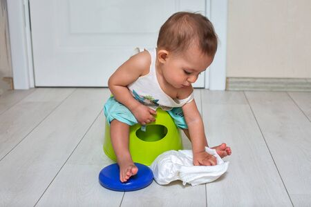 potty training concept. A cute little baby sits on a green pot and plays with a diaper in the room. close-up, soft focus, place for copy space