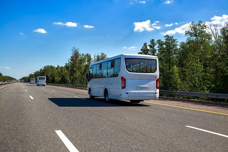 three new white minibuses ride in a convoy along the highway on a sunny day in summer. close up, back view