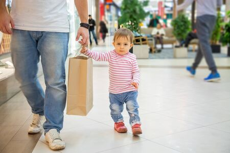 Black friday concept, shopping with children. little cute girl with dad holds a craft paper bag for shopping and looks at the camera. close-up, soft focus, in the background a shopping center in blur