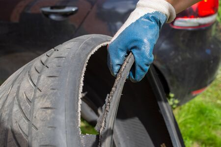 bad quality of wheels. the hand of the master in a blue glove holds the torn tire. on the background black car in blur Stock Photo