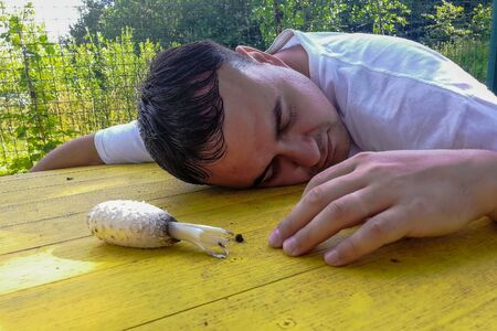 oncpt of poisoning, on a yellow street table lies a poisonous mushroom and an unconscious adult man with his eyes closed, summer sunny day. close-up. in the background green plants