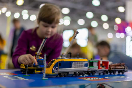 Moscow, Russia - October 04, 2019: yellow electric lego train with cranes. on background child plays with it in blur