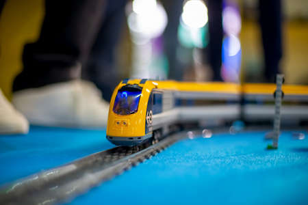 Moscow, Russia - October 04, 2019: toy yellow electric lego train rides on toy rails on a blue floor. legs in white sneakers in the background in blur. Editorial