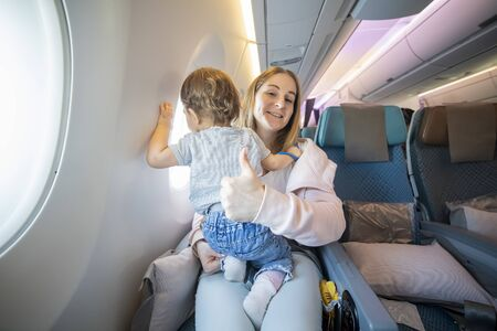 concept everything is OK. lofe is good. mom shows thumb up and looks at the camera with a smile. little cute toddler jumping on her knees with a young beautiful mother in an airplane chair.