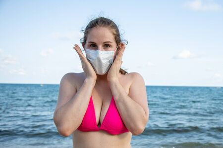 concept of fear of disease while traveling. young caucasian girl in a medical mask and in a swimsuit fearfully looks at the camera. In the background blue ocean.
