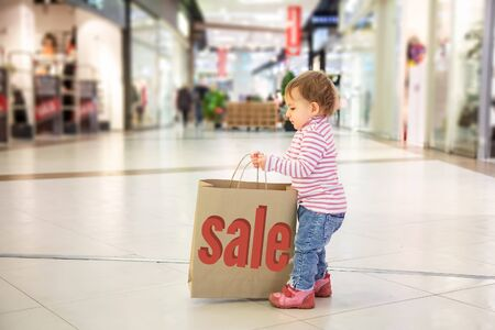 Black friday sale concept, nature friendly shopping. little cute baby girl picks up big craft paper bag for shopping with inscription sale. close-up, soft focus, in the background shops, side view Banque d'images