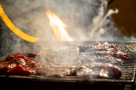in the evening, delicious juicy steaks on an open fire are grilled on a barbecue grill. close-up, soft focus. smoke is highlighted