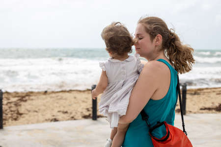 a young mother gently lovingly holds a baby girl in her arms against the background of the sea