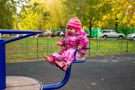 little toddler in warm winter overalls plays on the playground. soft focus Reklamní fotografie