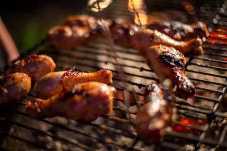 chicken drumsticks are grilled on a barbecue grill in the evening Banque d'images