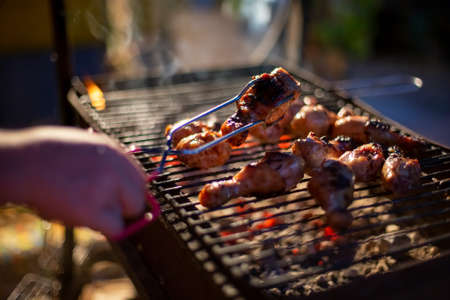 human hand turns chicken drumsticks on a barbecue grill with grilling tongs. cooking food on an open fire in the evening. backyard party