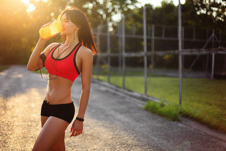 Young sport woman posing in fitness outfit with protein shake Stock Photo