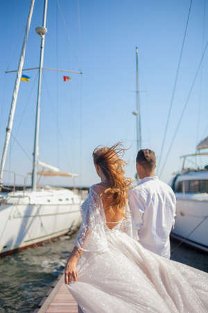 The newlyweds walk near the yacht club. The husbend leads the wife by the hand on the pier between the yachts. Wind waving the dress and the hair of the bride. Young couple back view Foto de archivo