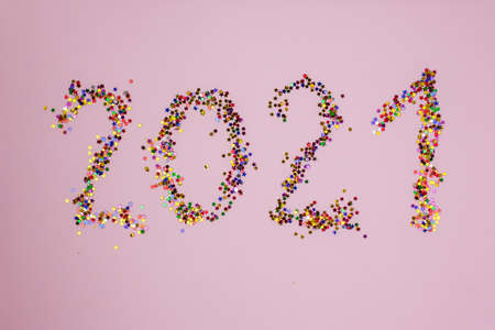 2021 in multicolor little stars on pink background. Figures 2021 made of glitter on pink backdrop. Happy 2021 New Year banner. Numbers made from multicolored confetti.