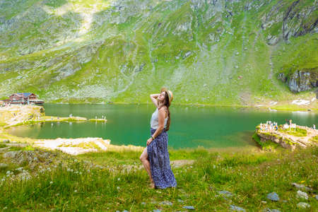 A sensual woman in a long dress and straw hat stands on the shores of Lake Balea against the backdrop of the high Romanian mountains. exciting holidays in the mountains in Transylvania, Romania