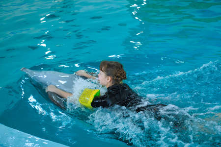 Happy little girl swimming with dolphins in Dolphinarium. Swimming, bathing and communication with dolphins. Treatment of children by means of dolphins. Dolphin therapy. Concept People and dolphins Stock Photo